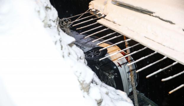 Karlı yolda kayan otomobil inşaat temeline düştü
